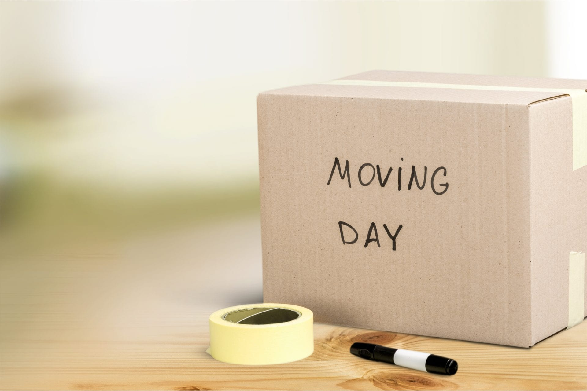 moving day box labeled with black sharpie sitting next to packing tape