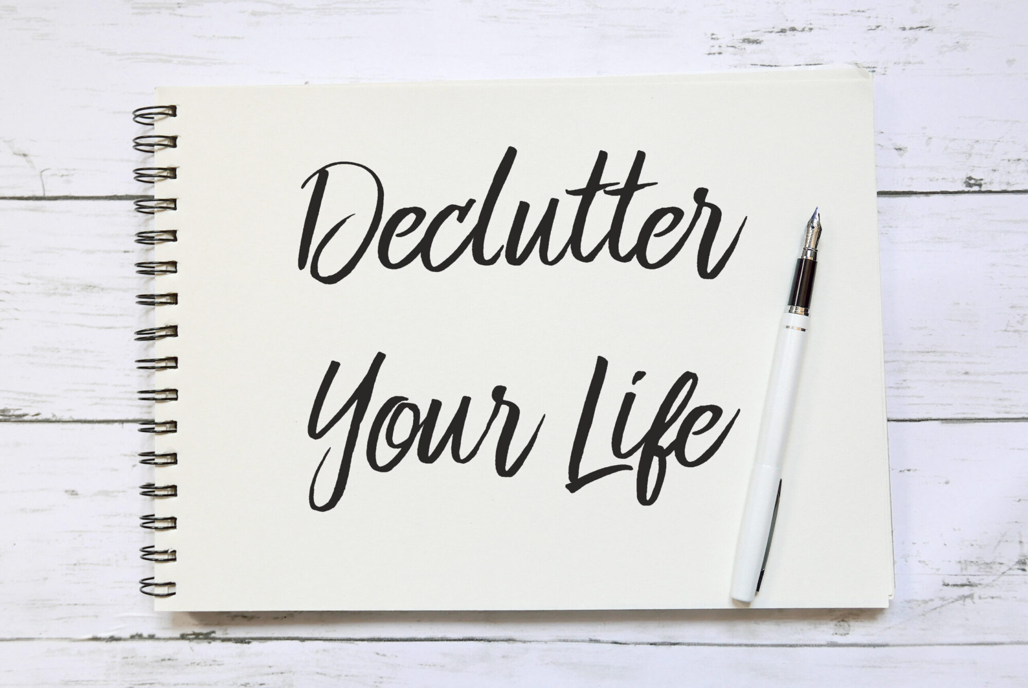Top view of pen and notebook written with Declutter Your Life on wooden background.